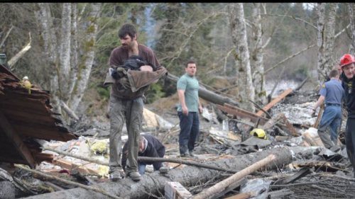 From KCPQ. Four men risked their lives to save this baby boy, ignoring the police's commands to stay off of the debris.